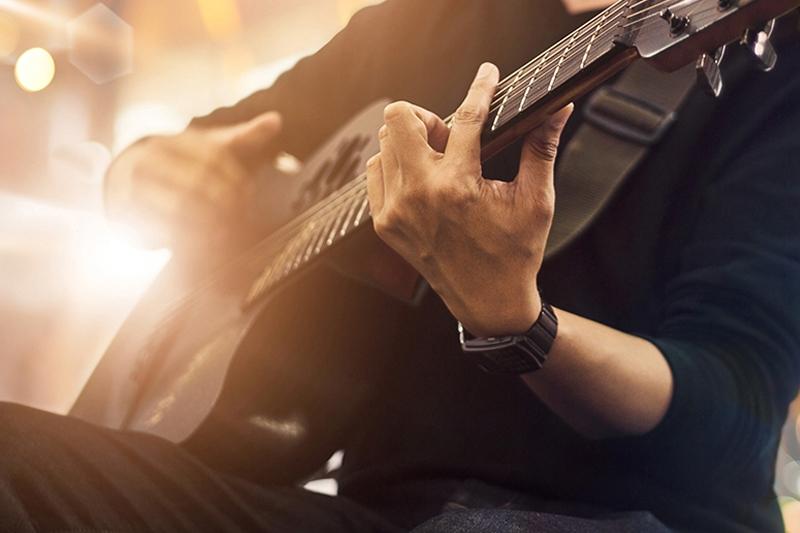 Guitarist spiller akustisk til firmaevent med aftenunderholdning.