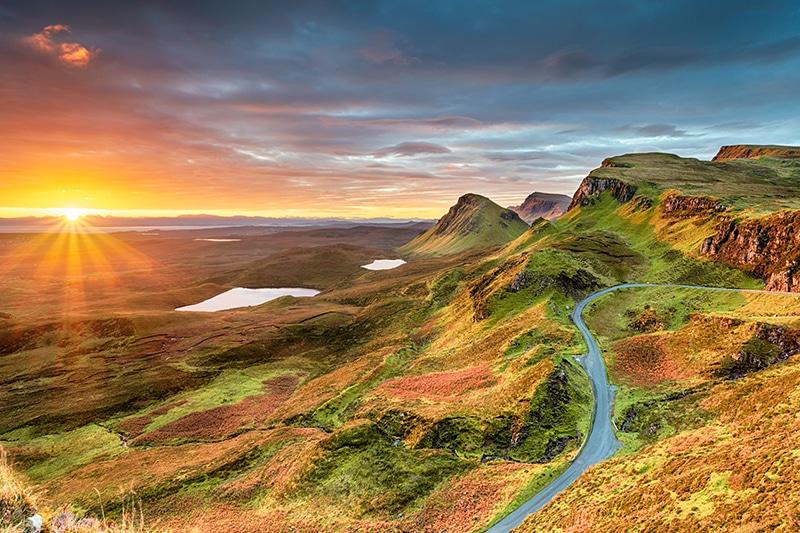 Skotsk højlandsstemning med solnedgang over flot landskab.