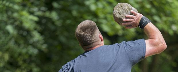 Mand i blå t-shirt kaster med en stor sten. Deltager i firmaevent med sjov teambuilding