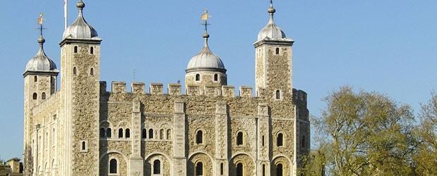 Tower of London med blå himmel og træer.