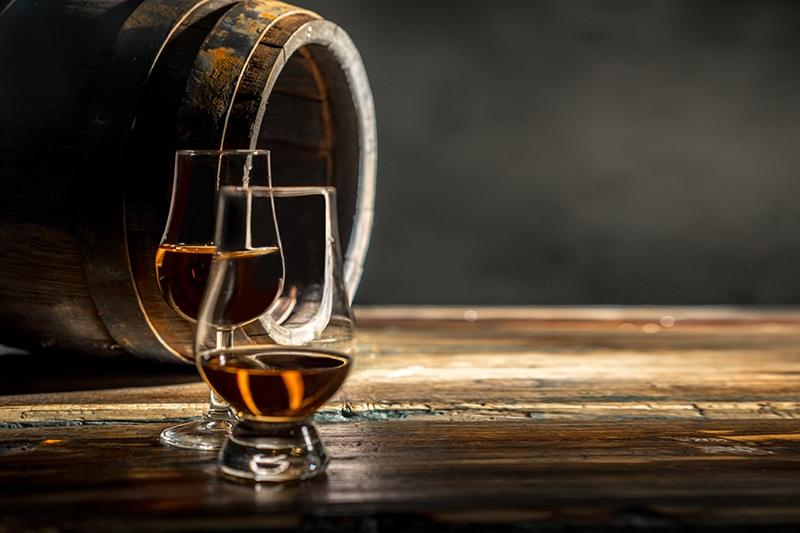 Træfad til whisky og to halvfyldte whiskyglas på et bord.